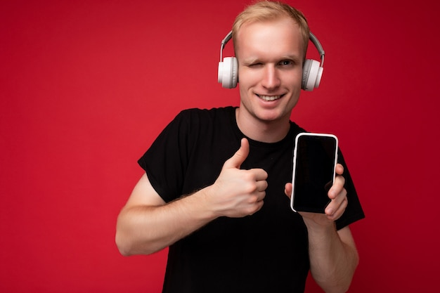 Winking handsome blonde young man wearing black t-shirt and white headphones standing isolated