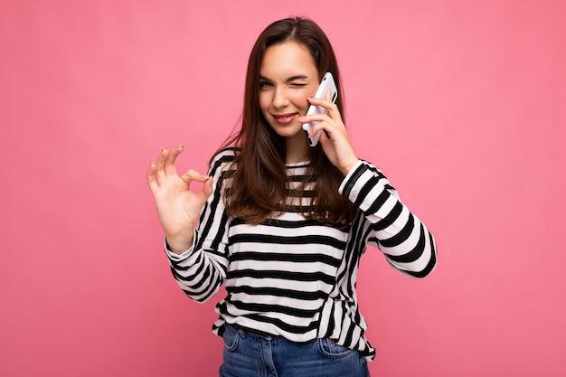 Подмигивая довольно счастливая молодая женщина разговаривает по телефону в полосатом свитере