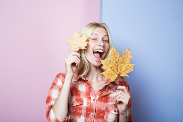 Winking woman in casual wear holds yellow leaves fashion trends for fall autumn woman with golden
