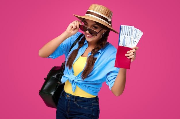 Подмигивая женщина-путешественница держит билет на самолет с паспортом. исследователь в джинсовой футболке и солнцезащитных очках. счастливая дама на изолированном фоне. студийный снимок