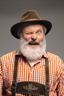 ウィンク。灰色のスタジオの背景に身振りで示す伝統的なオーストリアまたはバイエルンの衣装に身を包んだ幸せな年配の男性。コピースペース。お祝い、オクトーバーフェスト、お祭り、伝統のコンセプト。