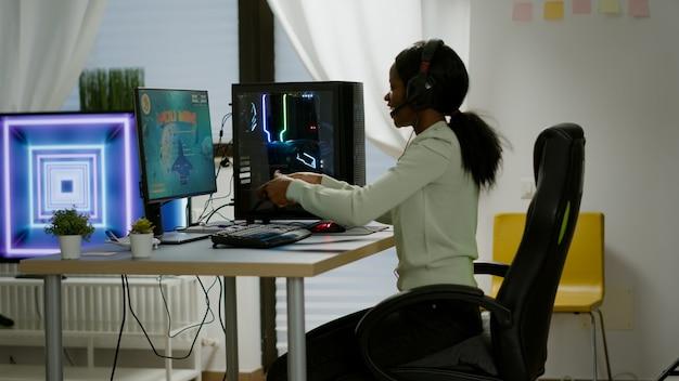 승자 흑인 게이머는 게임용 의자에 앉아 무선 컨트롤러로 공간 사수 비디오 게임을 하고 있습니다. rgb 강력한 개인용 컴퓨터에서 e스포츠 토너먼트를 위한 온라인 비디오 게임을 스트리밍하는 프로 사이버맨