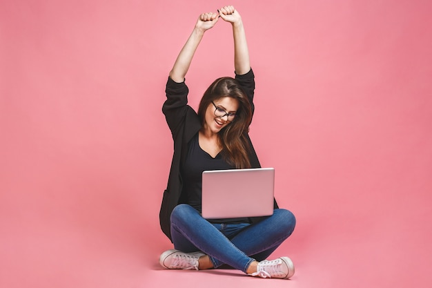 Winner business concept. portrait of happy woman in casual sitting on floor in lotus pose and holding laptop isolated over pink background