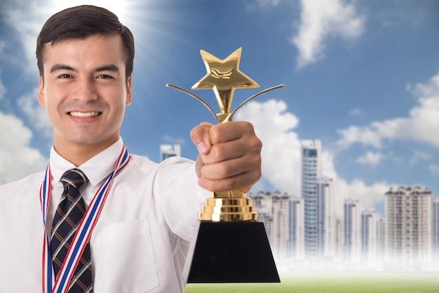 Победитель бизнесмен, держащий золотой трофей после успеха в своем бизнесе.