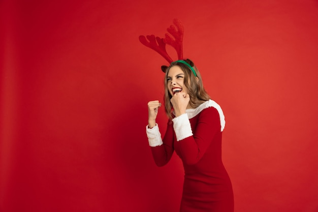 Winner, celebrating. concept of christmas, new year's, winter mood, holidays. . beautiful caucasian woman with long hair like santa's reindeer catching giftbox.
