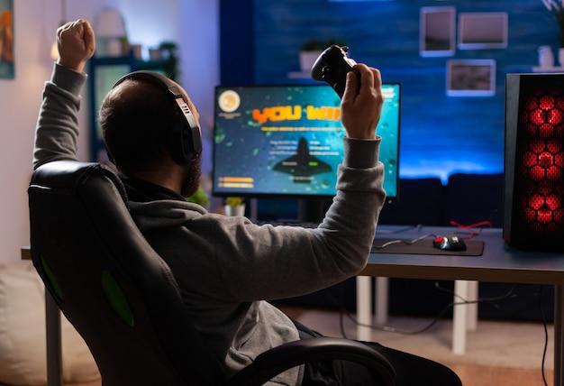勝者のゲーマーは、机のゲーミングチェアに座って、コントローラーでスペースシューティングビデオゲームをプレイします。ネオンライトのある部屋でeスポーツトーナメントのオンラインビデオゲームをストリーミングする男