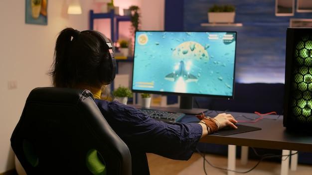 勝者のゲーマーが机のゲーミングチェアに座って、rgbキーボードとマウスでスペースシューティングビデオゲームをプレイする