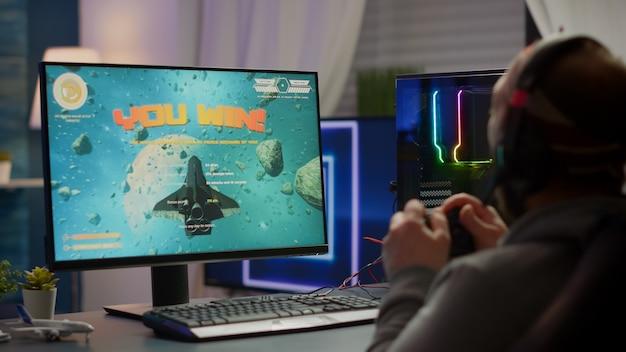 ゲーミングチェアに座って、ワイヤレスコントローラーでスペースシューティングビデオゲームをプレイする勝者ゲーマー。 rgbの強力なパーソナルコンピューターでeスポーツトーナメントのためのオンラインビデオゲームをストリーミングするプロサイバーマン