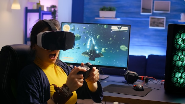 Giocatore vincitore che indossa occhiali per realtà virtuale, gioca a videogiochi sparatutto spaziali in camera con rgb