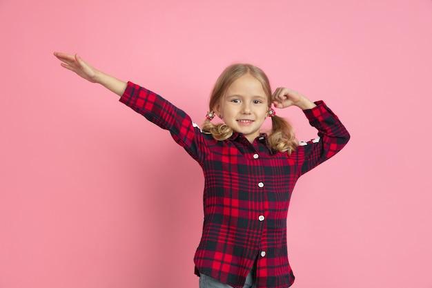 勝者のジェスチャー。ピンクのスタジオの壁に白人の少女の肖像画。