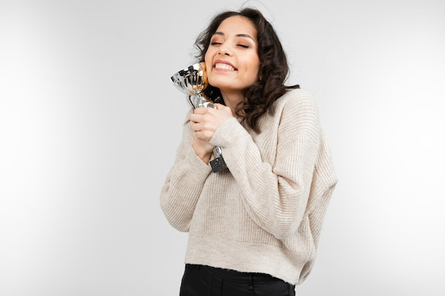 Winner girl holds her champion cup on gray background with copy space.