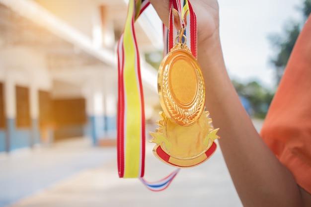 勝者の手は、彼らのビジネス、チャンピオンと賞コンセプトとショーチームの成功のための建物の背景をぼかして金メダルを保持