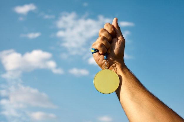 Winner hand raised and holding gold medal with ribbon against blue sky.