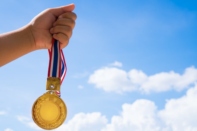 Winner hand raised holding gold medals with thai ribbon against blue sky.