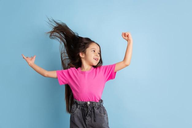 勝者、幸せ。青い壁に白人の少女の肖像画。ピンクのシャツを着た美しくてかわいい女性モデル。人間の感情、顔の表情、若者、子供時代の概念。
