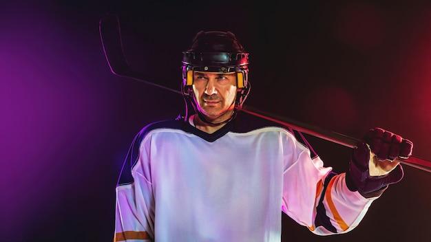 勝者。アイスコートと暗いネオン色の壁にスティックを持つ男性のホッケー選手。装備を身に着けているスポーツマン、ヘルメットの練習。スポーツ、健康的なライフスタイル、動き、健康、行動の概念。