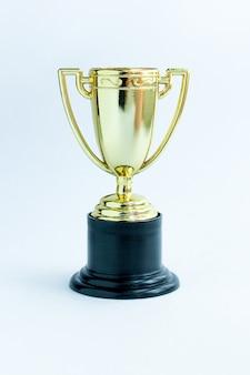 白い背景の上の勝者またはチャンピオンの金のトロフィーカップ。競争の勝利の最初の場所。勝利または成功のコンセプト。