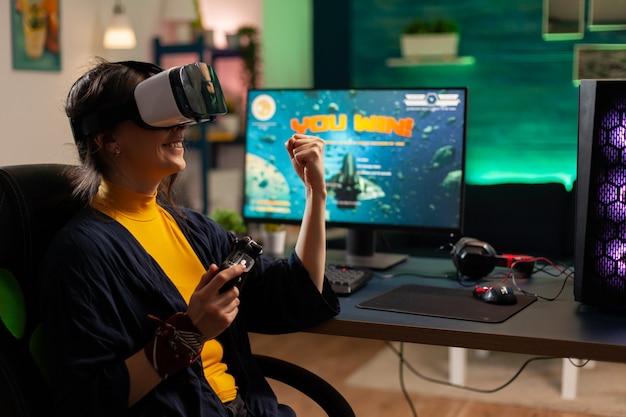 ゲームホームロムでバーチャルリアリティビデオゲームをプレイするコンソールを保持している勝者プレーヤー。最新の機器を使用して強力なコンピューターで新しいグラフィックスを使用してオンラインビデオゲームをストリーミングするプロゲーマー。
