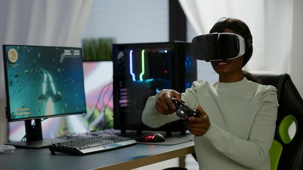 バーチャルリアリティを使用してゲームルームでビデオゲームをプレイするジョイスティックを保持している勝者プレーヤー。最新の機器を使用して強力なコンピューターで新しいグラフィックスを使用してオンラインビデオゲームをストリーミングするプロゲーマー。