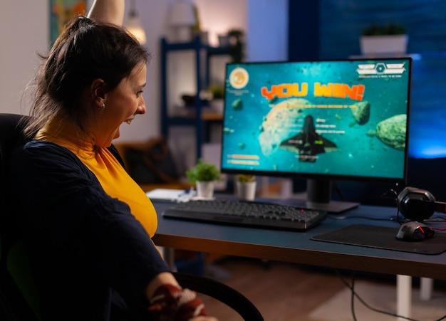 勝者は机のゲーミングチェアに座って、ジョイスティックでスペースシューティングビデオゲームをプレイします。ネオンライトのある部屋でeスポーツトーナメントのオンラインビデオゲームをストリーミングする女性