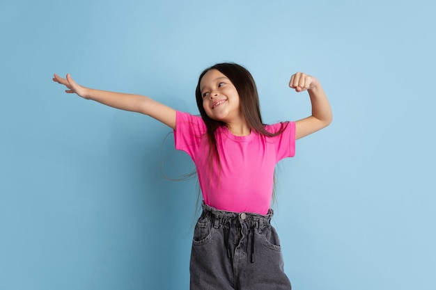 Winner's gesture. caucasian little girl's portrait on blue studio wall