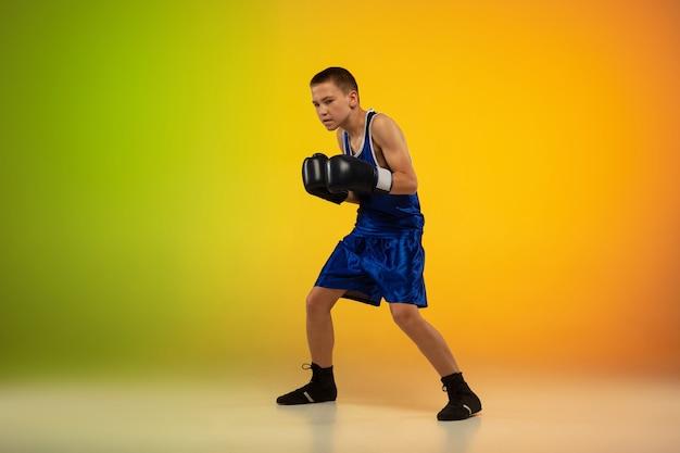 勝者。アクションで10代のプロのボクサートレーニング、ネオン光のグラデーションの背景に分離された動き。キック、ボクシング。スポーツ、運動、エネルギー、ダイナミックで健康的なライフスタイルのコンセプト。