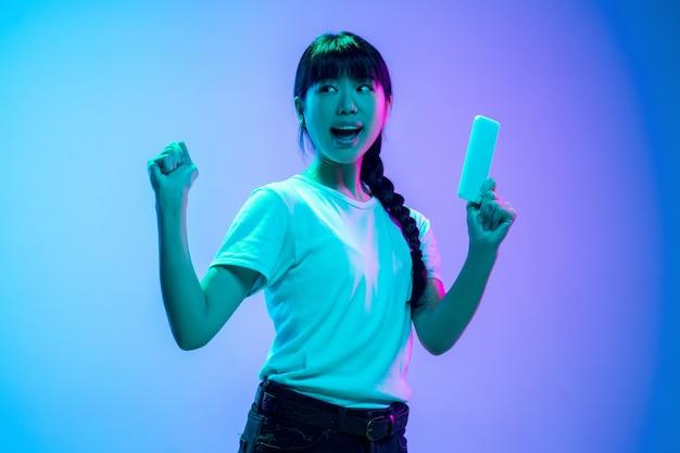 전화로 승자입니다. 네온 불빛에 그라데이션 파란색 보라색 스튜디오 배경에 젊은 아시아 여성의 초상화. 젊음, 인간의 감정, 표정, 판매, 광고의 개념. 아름 다운 갈색 머리 모델입니다.