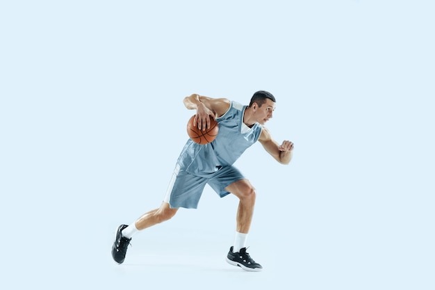우승자. 활동 중인 팀의 젊은 백인 농구 선수, 파란색 배경에 격리된 점프 동작. 스포츠, 운동, 에너지 및 역동적이고 건강한 생활 방식의 개념. 훈련, 연습.