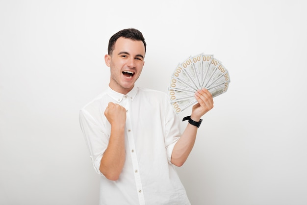 Победитель молодой человек, держащий кучу долларов на белом фоне.