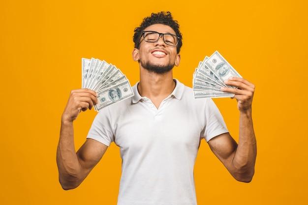 Победитель! молодой богатый афро-американский мужчина в футболке с сюрпризом держит долларовые купюры