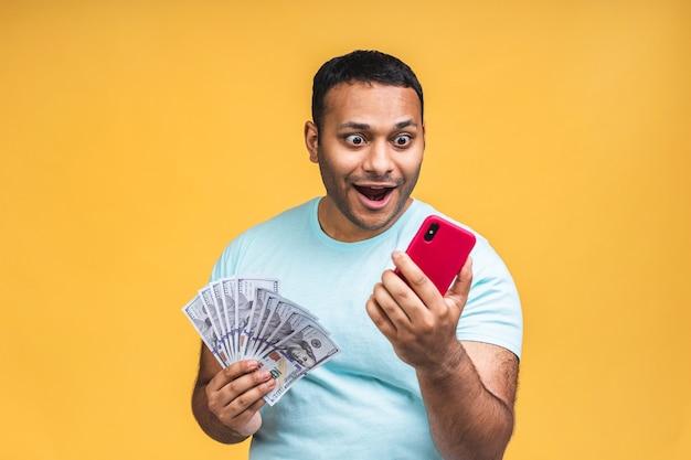 勝者!黄色の壁の背景に分離された驚きとお金のドル紙幣をカジュアルに保持している若い金持ちの幸せなアフリカ系アメリカ人のインドの黒人男性。携帯電話を使う。