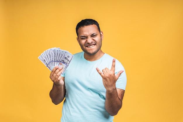 勝者!黄色の壁の背景に分離された驚きとお金のドル紙幣をカジュアルに保持している若い金持ちの幸せなアフリカ系アメリカ人のインドの黒人男性。