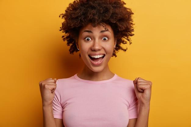 승리와 성공. 활기차고 긍정적 인 곱슬 곱슬 한 젊은 여성이 주먹을 움켜 쥐고, 활짝 웃으며, 낙관적이며, 인생에서 일어난 멋진 이벤트를 응원하고, 노란색 벽에 고립되어 승자처럼 느껴집니다.