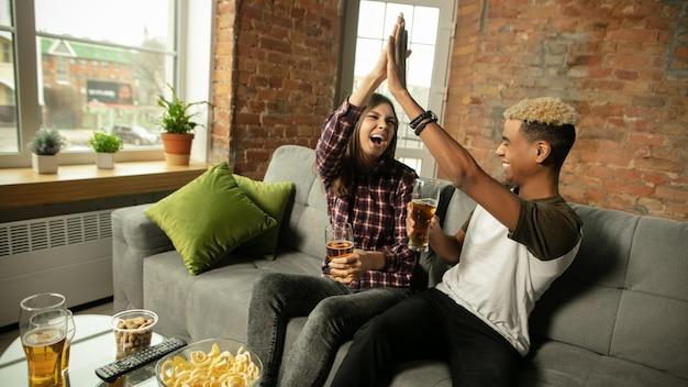 승리. 흥분된 커플, 스포츠 경기를 보는 친구, 집에서 chsmpionship. 다민족 친구.