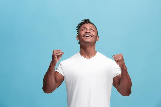 Достигнув успеха, афро-американский мужчина счастлив в восторге, празднуя победу.