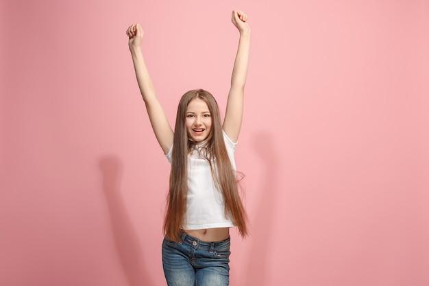 勝者であることを祝う成功の幸せな十代の少女。ピンクのスタジオの壁に白人女性モデルのダイナミックな画像。勝利、喜びの概念。人間の顔の感情の概念。トレンディな色