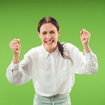 Donna felice di successo vincente che celebra essere un vincitore. immagine dinamica del modello femminile caucasico sulla parete verde dello studio. vittoria, concetto di gioia. concetto di emozioni facciali umane. colori alla moda