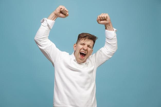 勝者になることを祝う幸せな有頂天の成功男。男性モデルのダイナミックでエネルギッシュなイメージ