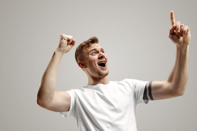 勝者であることを祝う成功者の幸せな恍惚とした勝利。男性モデルのダイナミックでエネルギッシュなイメージ