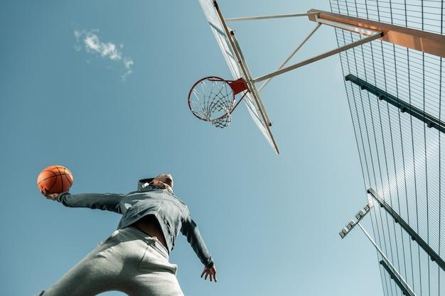 이기는 던지기. 승리 던지기를하는 동안 점프하는 농구 선수의 낮은 각도