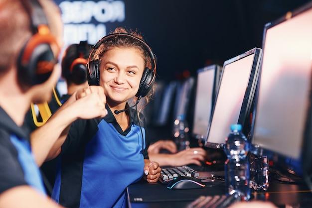 勝ちました。 esportsトーナメントに参加している間、拳をぶつけて成功を祝う2人の若い幸せなプロのサイバースポーツゲーマー。オンラインビデオゲーム