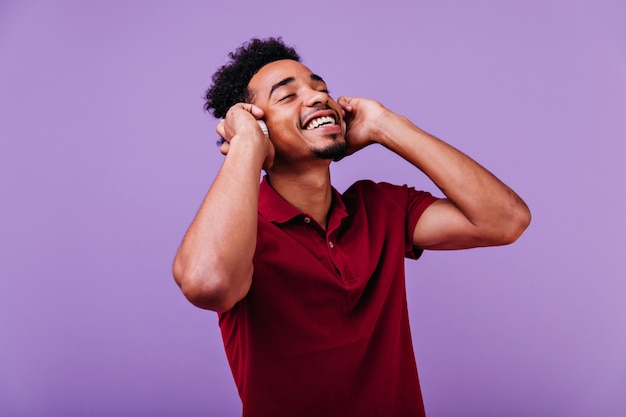 Winsome african man in red t-shirt posing with eyes closed and shy smile. indoor photo of handsome black model listening music.