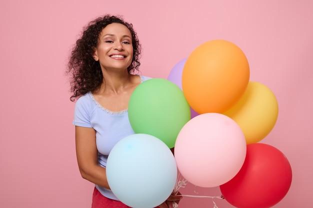 魅力的な歯を見せる笑顔で魅力的な混血の女性、明るいカラフルなヘリウム風船を持って幸せな反応を持っている、誕生日を祝う、カメラを見て、ピンク色の背景で隔離