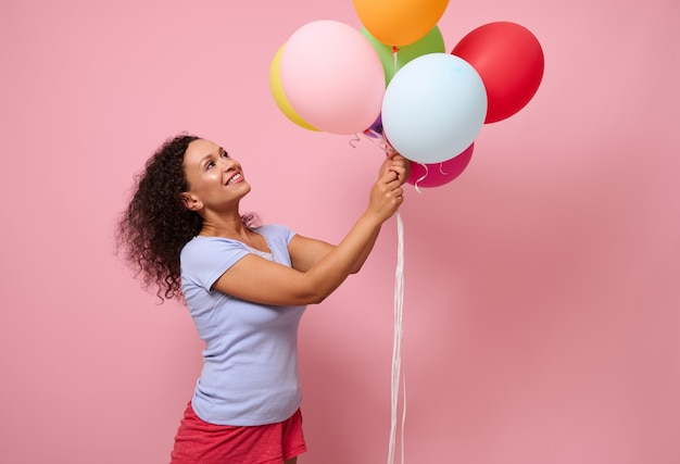 ピンク色の背景に立って、彼女の手でカラフルな明るい風船を見上げて笑っている青いtシャツの魅力的な美しい巻き毛の髪の女性。コピースペースと記念日のコンセプト