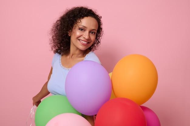 魅力的な歯を見せる笑顔で魅力的な美しい混血の女性、明るいカラフルなヘリウム風船を持って幸せな反応を持っている、誕生日を祝う、カメラを見て、ピンク色の背景で隔離