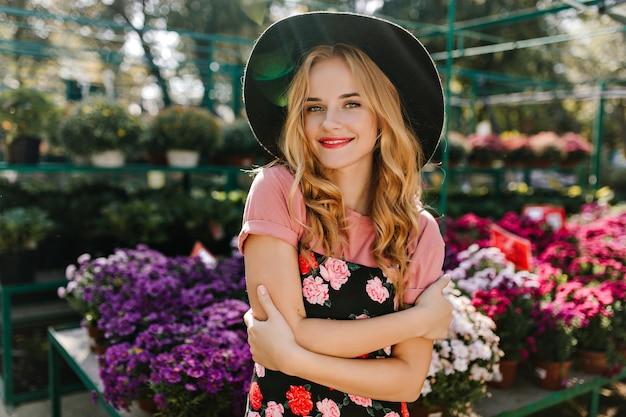 오렌지에 포즈 winsome blinde 여자입니다. 화려한 꽃 옆에 서있는 검은 모자에 즐거운 백인 여자의 실내 초상화.