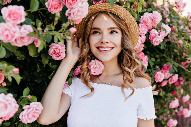 Winsome blue-eyed girl in summer hat posing in garden. outdoor portrait of blithesome curly woman laughing with roses