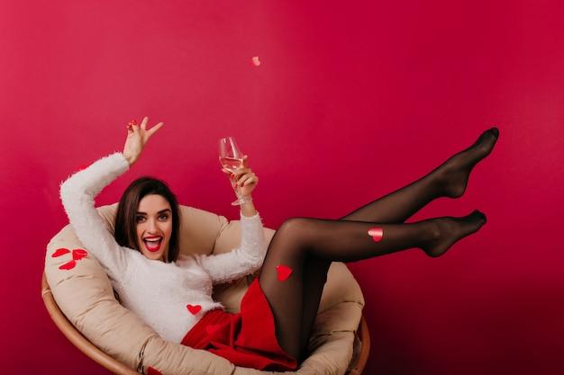 Очаровательная девушка брюнетка в белом свитере, лежа в кресле