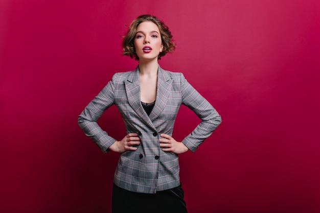 クラレットの壁に隔離されたツイードジャケットの自信を持って女の子のポーズの短い散髪の魅力的なビジネス女性。