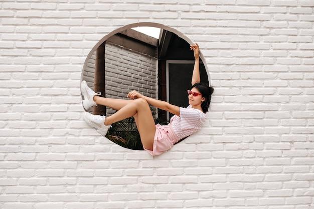 レンガの壁に座っている魅力的な白人女性。都市の背景にポーズをとって嬉しい日焼けした女性の屋外ショット。